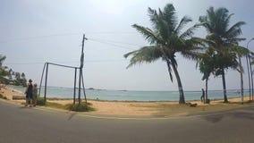 HIKKADUWA, SRI LANKA - MÄRZ 2014: Zeitlupe der Ansicht über den schönen Strand mit Palmen von beweglichem Fahrzeug stock footage