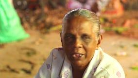 HIKKADUWA, SRI LANKA - MAART 2014: Portret van een lokaal die bejaarde bij Hikkaduwa-Zondagmarkt, voor zijn brede waaier van vers stock footage