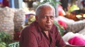 HIKKADUWA, SRI LANKA - MAART 2014: Portret van lokaal bejaarde met paan bevlekte die mond bij Hikkaduwa-markt, voor zijn breed r  stock video