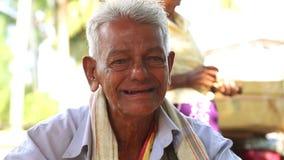 HIKKADUWA, SRI LANKA - MAART 2014: Portret van lokaal die bejaarde bij Hikkaduwa-Zondagmarkt, voor zijn brede waaier van vers wor stock video