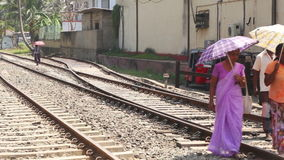 HIKKADUWA, SRI LANKA - MARCH 2014: View of local women walking on railway track on the way to the market with umbrellas to protect stock video footage