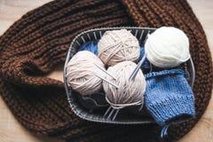 Hilado beige, blanco y azul, agujas que hacen punto en la cesta y una bufanda marrón fotografía de archivo libre de regalías