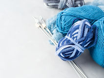 Hilado de lana azul con las agujas que hacen punto en fondo gris Fotografía de archivo libre de regalías