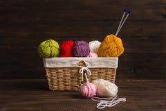Hilado de lanas en bobinas con las agujas que hacen punto en mimbre Fotos de archivo