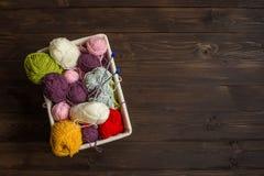 Hilado de lanas en bobinas con las agujas que hacen punto en mimbre Fotos de archivo libres de regalías
