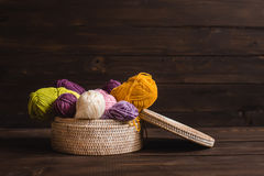 Hilado de lanas en bobinas con las agujas que hacen punto en mimbre Imágenes de archivo libres de regalías