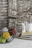 Hilado de lanas en una cesta del vintage, libros y el conejito de pascua en la tabla de madera ligera rústica Imagen de archivo libre de regalías