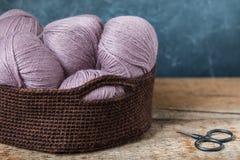 Hilado de lanas rosado con las tijeras en la cesta hecha a ganchillo Imagenes de archivo