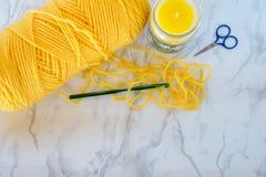 Hilado, gancho y tijeras amarillos del ganchillo con la vela en fondo neutral Imagen de archivo