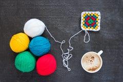 Hilado multicolor, un adorno hecho a ganchillo y café Fotos de archivo