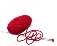 Hilado rojo con las agujas que hacen punto en un fondo blanco Fotos de archivo libres de regalías