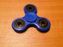 Hilandero aislado en el fondo de madera Hilandero azul del juguete Hilandero de la mano aislado en fondo de madera Spiner del jug Foto de archivo libre de regalías