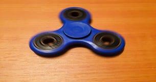 Hilandero aislado en el fondo de madera Hilandero azul del juguete Hilandero de la mano aislado en fondo de madera Spiner del jug Imagen de archivo libre de regalías