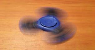 Hilandero aislado en el fondo de madera Hilandero azul del juguete Hilandero de la mano aislado en fondo de madera Spiner del jug Fotografía de archivo libre de regalías