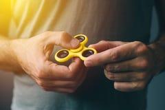 Hilandero amarillo de la persona agitada en la mano masculina Fotografía de archivo