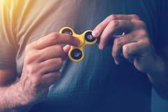 Hilandero amarillo de la persona agitada en la mano masculina Imagenes de archivo