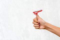 Hilandero de la persona agitada Hilandero rojo de la mano, juguete de la mano que inquieta que gira en la mano del ` s del niño A Imagen de archivo