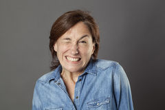 Hilarious middle aged woman showing teeth in trying to wink Royalty Free Stock Image