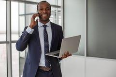 Optimistic businessman is having pleasant communication on mobile phone stock photography