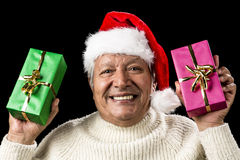 Hilarious Senior Offering Green And Pink Gift. Cheerful and excited aged gentleman waving two wrapped presents like flags. Red Father Christmas hat. Sparkling Stock Photography