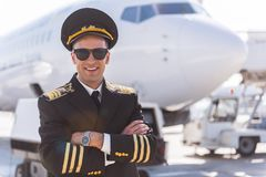 Hilarious smiling aviator locating near plane. Merry pilot wearing sunglasses is standing afore aircraft and looking at camera with bright smile. He crossing Stock Images