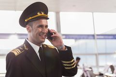 Hilarious smiling aviator using phone Stock Photo