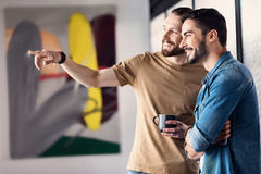 Hilarious smiling male people planning something. Glad interested men are standing in office and looking ahead with wide smile. Colleague is pointing forward royalty free stock images
