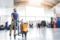 Hilarious smiling man carrying luggage. Cheerful male passenger is walking through airport-foyer with baggage. He glancing ahead with smile. Low angle. Copy Stock Photo