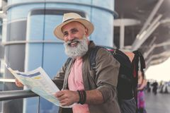 Hilarious smiling old man ready for journey. Cheerful elder bearded tourist wearing hat is holding unfolded map and looking at camera with bright smile. Waist up Royalty Free Stock Photos