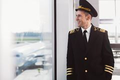 Hilarious smiling pilot standing in terminal. Joyous aviator is leaning against glass wall and looking at planes with wide smile. Waist-up portrait. Copy space Stock Photos