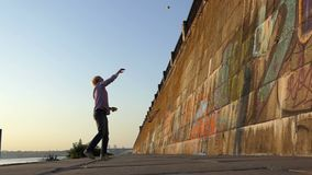 Sportive man throws a ball on a river bank wall in slo-mo. A hilarious view of a young man who throws a tennis ball on a stony wall of the Dnipro river bank and stock video