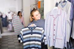 Hilarious woman choosing pajamas top for man in shop Royalty Free Stock Images