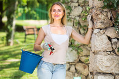 Hilarious young woman holding horticultural tools in garden. On sunny day Royalty Free Stock Photo