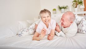 Hilariuos happy seniors having fun. And playing around in bedroom royalty free stock image