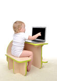 Сhild baby girl toddler sitting computer laptop pointing finget Stock Photography
