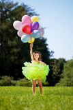 �hild with a bunch of balloons in their hands Stock Photos