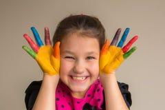 Hild com as palmas e mãos pintadas coloridas com pinturas da cor imagens de stock