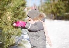 Сhild decorates a сhristmas tree balls outdoors Royalty Free Stock Image
