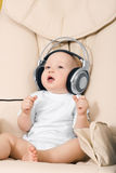 The hild and ear-phones. The child sits and listens to music in ear-phones Royalty Free Stock Images