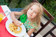 Сhild eating potato chips in the cafe Stock Photography