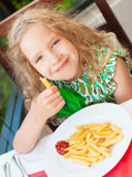 Сhild eating potato chips in the cafe Royalty Free Stock Photos