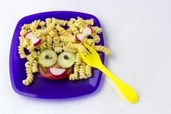Hild food. Funny food. Plate with pasta. Child food. Funny food. Plate with pasta with vegetables in the form of funny face. Children`s menu. Children`s lunch stock photo