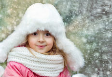 Сhild girl outdoors in snwy winter background. Royalty Free Stock Photos