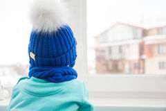 Сhild looking into window with hope during cold winter day while cold Stock Image