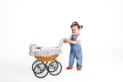 Сhild playing with a baby carriage Royalty Free Stock Photography