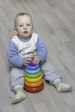 Сhild plays with a pyramid. Little child plays with a toy rainbow pyramid Stock Photography