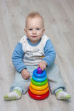 Сhild plays with a pyramid. Little child plays with a toy rainbow pyramid Royalty Free Stock Image