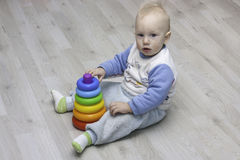 Сhild plays with a pyramid. Little child plays with a toy rainbow pyramid Royalty Free Stock Photo