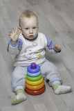 Сhild plays with a pyramid. Little child plays with a toy rainbow pyramid Stock Photo