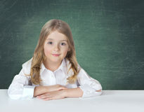 Сhild school girl in white shirt sitting at the table on blackb Stock Photos